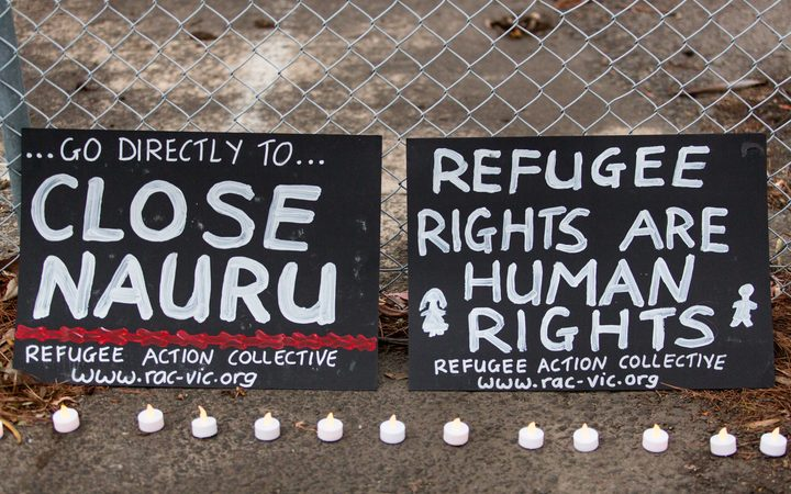 Two banners and candles at the gates of a refugee detention centre during a candlelight vigil. Asanka Brendon Ratnayake / Anadolu Agency