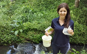 Amanda Valois in Hamilton's Donny Park holding mostly plastic rubbish she picked up along the 100 metre walk from the road to the stream.