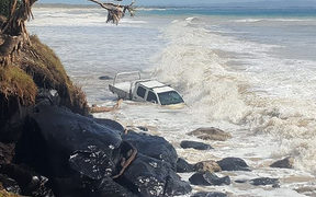 A vehicle at Rainbow Beach swamped by waves in a large swell created by Cyclone Oma.
