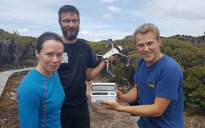 Flying kakapo sperm - a world first. DOC's Kakapo Recovery Team manager Deidre Vercoe with 'spermcopter' drone pilot Anton Marsden, and sperm expert Andreas Bublat holding a tiny vial of kakapo sperm.