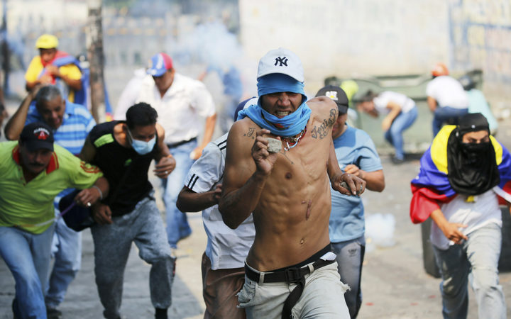 Demonstrators run from tear gas fired by Bolivarian National Guard officers during clashes in Urena, Venezuela, near the border with Colombia, Saturday, Feb. 23, 2019.