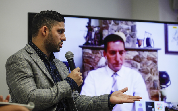 David Miranda, left, looks on as his partner Glenn Greenwald speaks via video link during a Russian discussion about the right to privacy.