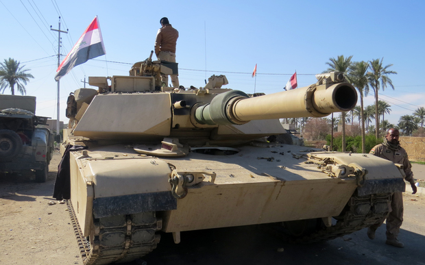 Iraqi security forces stand next to a tank as they clear al-Sajarya district on the eastern outskirts of Ramadi, the capital of Anbar province.