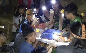 In this undated photo released by Indonesian Search And Rescue Agency (BASARNAS) rescuers evacuate a survivor from a collapsed gold mine in Bolaang Mongondow, North Sulawesi, Indonesia.