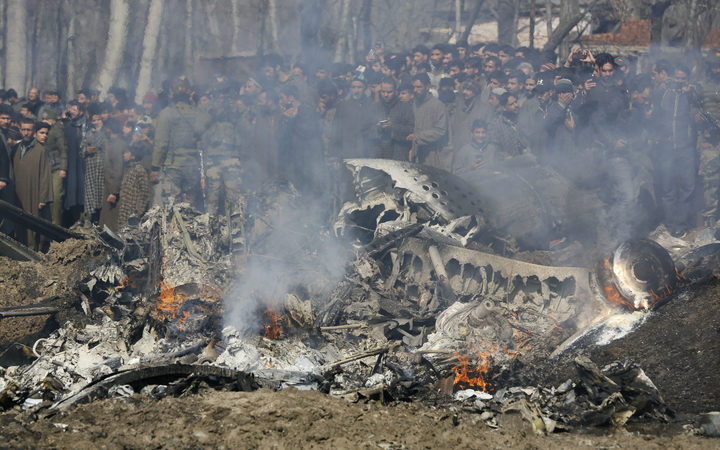 Kashmiri villagers gather near the wreckage of an Indian aircraft after it crashed in Budgam area, outskirts of Srinagar, Indian controlled Kashmir, on 27 February.