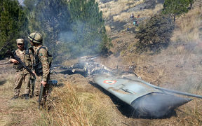 Pakistani soldiers stand next to what Pakistan says is the wreckage of an Indian fighter jet shot down in Pakistan-controlled Kashmir.