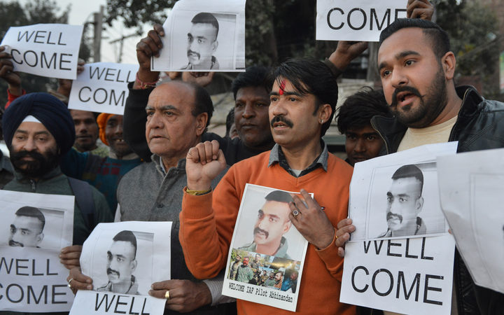 Indian people hold placards and photographs of Indian Air Force pilot Abhinandan Varthaman, as they celebrate the announcement of his soon release, in Amritsar.
