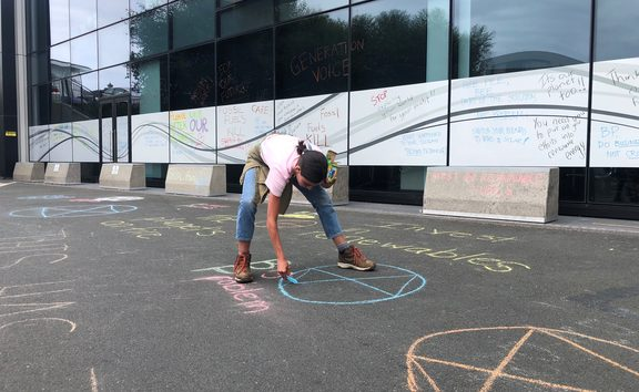 A protestor, Danielle Jones, makes her mark on the concrete outside BP's Auckland office.