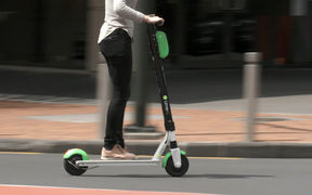 Person riding a Lime scooter in Auckland city.