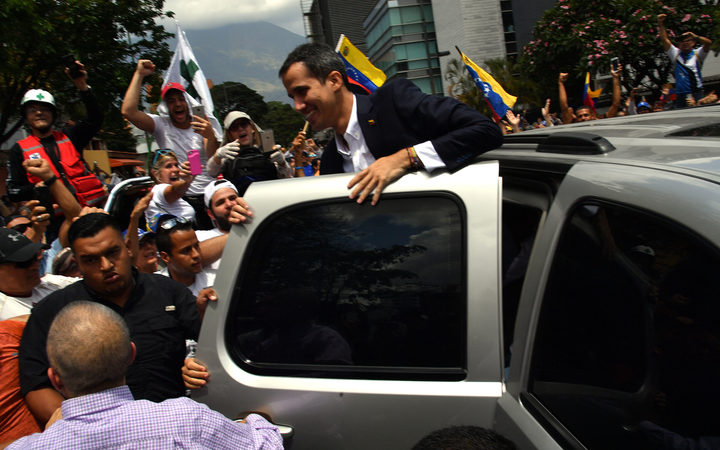 Venezuelan opposition leader and self-proclaimed acting president Juan Guaido greets supporters upon his arrival in Caracas on March 4, 2019.