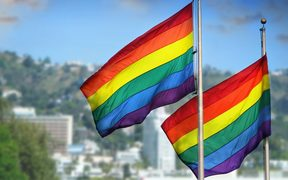 21543261 - a pair of rainbow flags waving in wind against city background of west hollywood, california