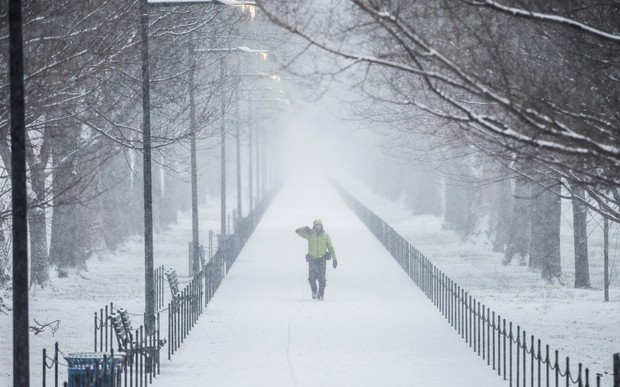 A man walks along the National Mall as the snow begins to fall in Washington, United States.
