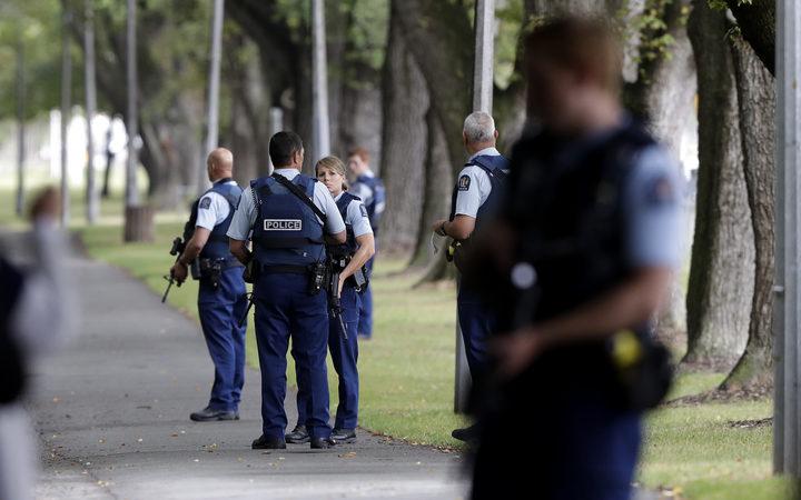 警察在新西兰克赖斯特彻奇市中心一座清真寺对面的公园里守望