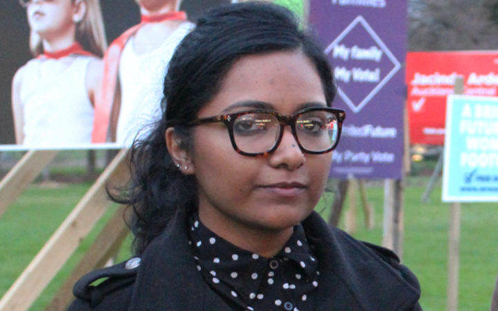 A photo of Saziah Bashir and Fern Seato outside election campaign billboards