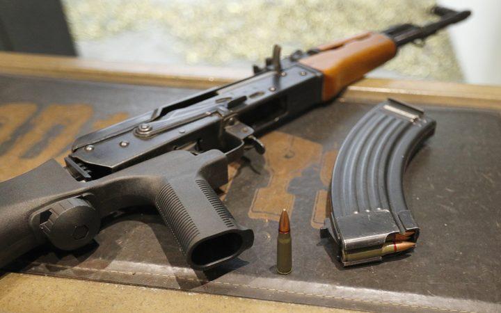 一个7,62X39mm的圆形紧挨着一个30圆形的弹匣和一个安装了凸起的AK-47。