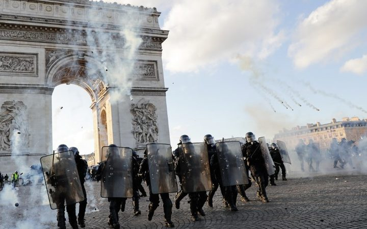 Riot police charge using tear gas canister at the Arc de Triomphe on the Place de l'Etoile in Paris