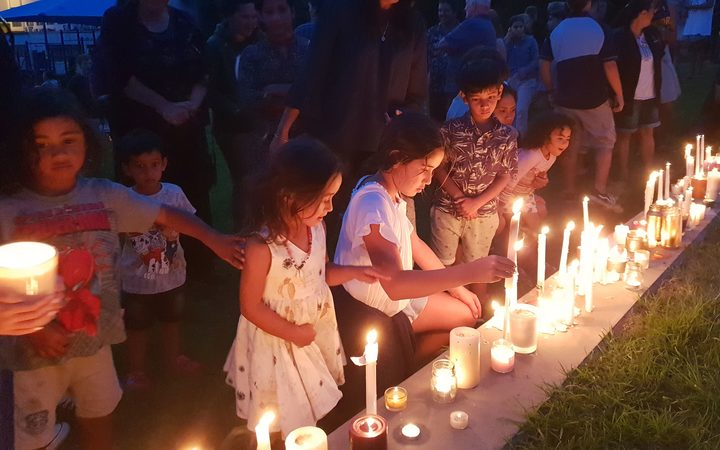 Children light candles at a vigil in Whangarei,
