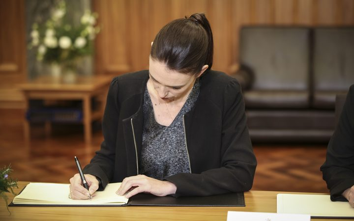 Prime Minister Jacinda Ardern signs the Condolence Book.