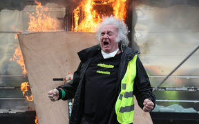 A Yellow Vest protester gestures in front of a newsstand set alight during clashes with riot police forces on the Champs-Elysees in Paris on March 16.
