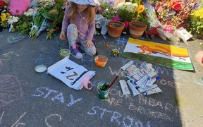 Ash Boraman-Ritchie paints a message outside Al Huda Mosque in Dunedin.