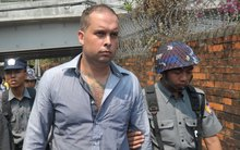 New Zealand bar manager Philip Blackwood, centre, is escorted by police as he arrives at a court for a hearing in Yangon on 17 March 2015.