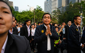 Thailand's Prime Minister Prayut Chan-O-Cha (C) greets people at Lumphini Park in Bangkok on 20 March, 2019.