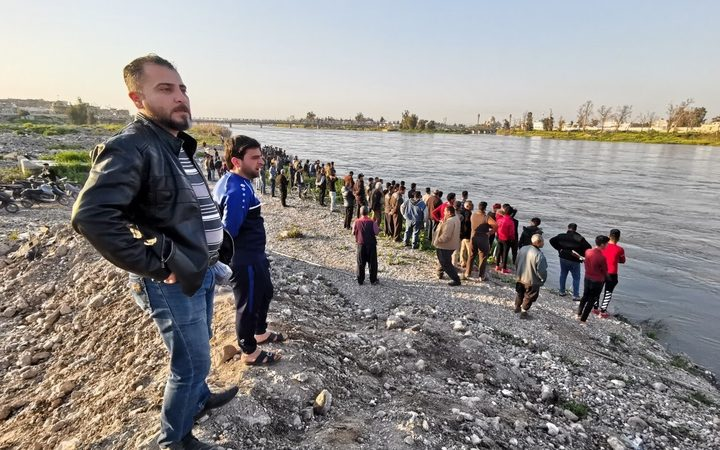 MOSUL, IRAQ - MARCH 21: Citizens follow the search and rescue operations around the site after a ferryboat sank in Iraq's Tigris River, leaving at least 55 people dead and more than 100 others injured, in Mosul, Iraq. The ferryboat was reportedly carrying 170 passengers when it sank near Mosul.