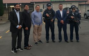 Community members from the Rasol-O-Allah Islamic Centre with armed police.
