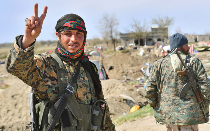 A picture taken on March 23, 2019 shows a fighter of the US-backed Kurdish-led Syrian Democratic Forces (SDF) flashing the V for victory sign in the fallen Islamic State group's last bastion in the eastern Syrian village of Baghuz after defeating the jihadist group.