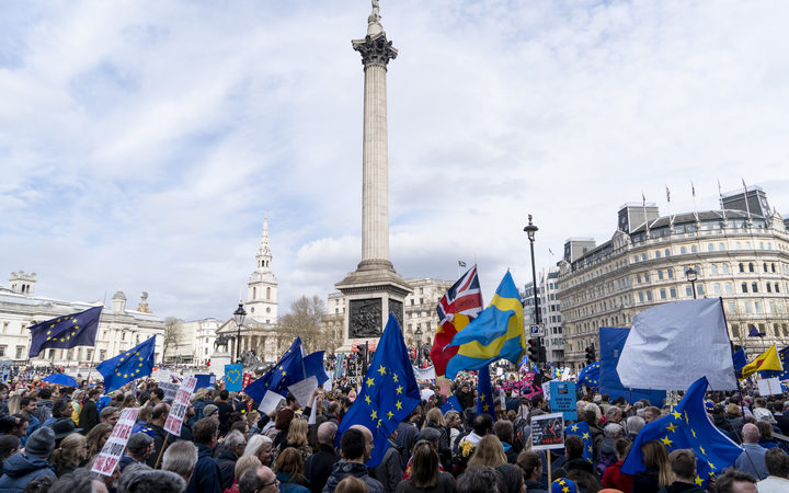 People hold up placards and European Union flags as they pass Trafalgar Square on a march and rally organised by the pro-European People's Vote campaign for a second EU referendum in central London on March 23, 2019.