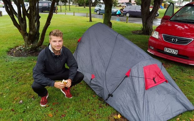 Freedom camper Malte Kellermann crouches next to his tent near Addington Park in Christchurch.