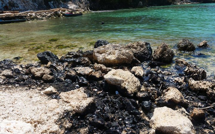 Oil blackened rocks on the seashore of Rennell Island. February 2019