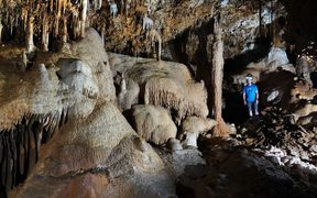 Adam Hartland in a cave filled with speleothems such as stalactites, stalagmites and flowstones, all of which hold records of past climate.