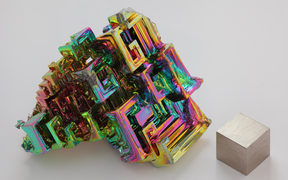 The chemical element bismuth as a synthetic crystal. The iridescent surface is a very thin layer of oxidation. Beside it is a high purity (99.99 %) 1 cm3 cube of bismuth for comparison.