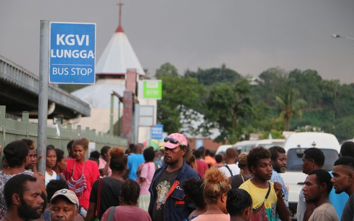 People at a bus stop in Honiara, Solomon Islands