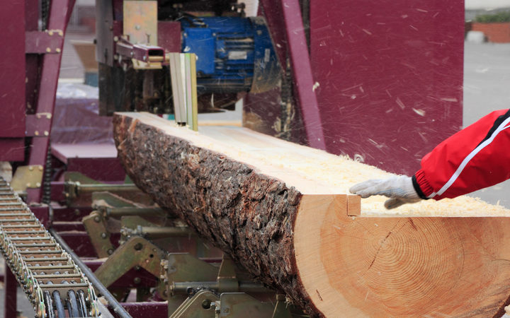 Sawing boards from logs with circular sawmill.