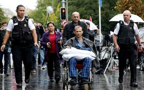 Temel Atacocugu (c), a survivor of the  mosque attacks, leaves the Christchurch District Court after the alleged gunman's second court appearance.
