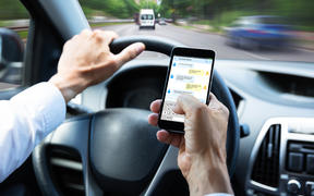 Close-up Of A Man's Hand Typing Text Message On Mobile Phone While Driving Car