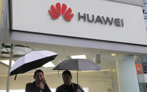 FILE - In this Thursday, March 7, 2019 file photo, two men use their mobile phones outside a Huawei retail shop in Shenzhen, China's Guangdong province.
