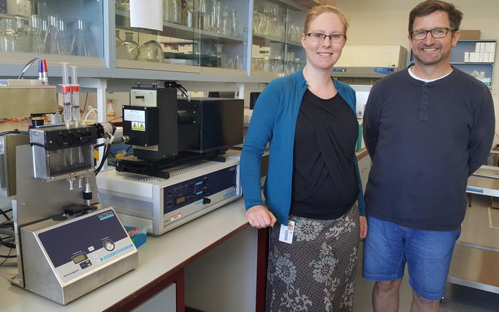 Erica Prentice and Vic Arcus in the lab, standing next to the machine they use to test enzyme reactions at different temperatures.