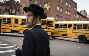 A man walks past school buses in a South Williamsburg neighborhood. A public health emergency has been declared in the  area.