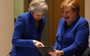 Theresa May and Angela Merkel share a laugh over something on a tablet during the crunch summit in Brussels.