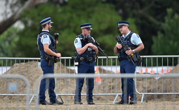 Armed police officers patrol gravesites for victims in Christchurch this morning.