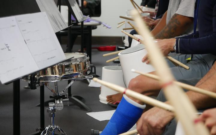 Participants of a music course at Chch men's prison drum on buckets with members of the CSO