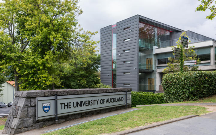 Auckland, New Zealand - March 1, 2017: Sign and logo of University of Auckland set near modern dark gray offices in green park like environment. Gray sky.