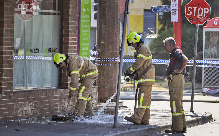 Firemen wash away bloodstains after a security guard was shot dead with another man fighting for his life after a drive-by shooting outside a popular Melbourne nightclub.