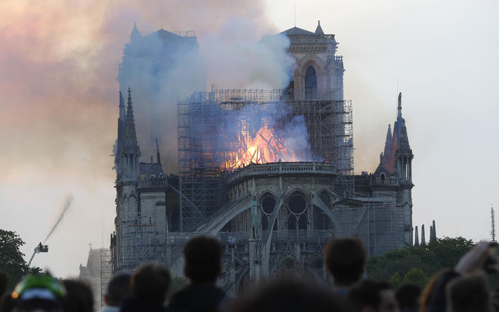 People watch as flames and smoke rise from Notre-Dame cathedral.