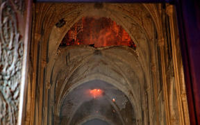 Stone vaults inside Notre-Dame Cathedral with flames are seen through the damaged roof.