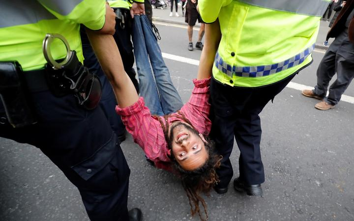 Police officers remove a climate change activist at Oxford Circus on the third day of its blockade by environmental protest group Extinction Rebellion.