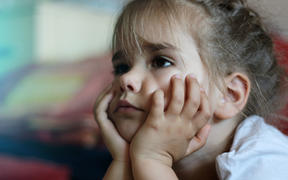 A photo of a little girl lying on the sofa with hands on chin watching the television and looking worried